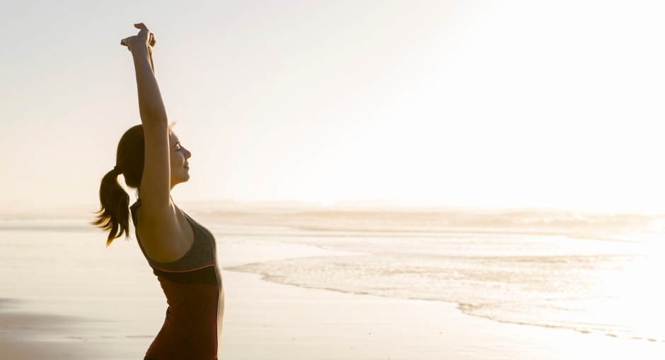 A woman doing stretching exercises on the beach early in the morning for better posture