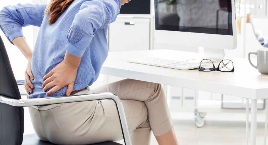 Business woman with back pain because she ignored the ergonomic risk factor of poor posture