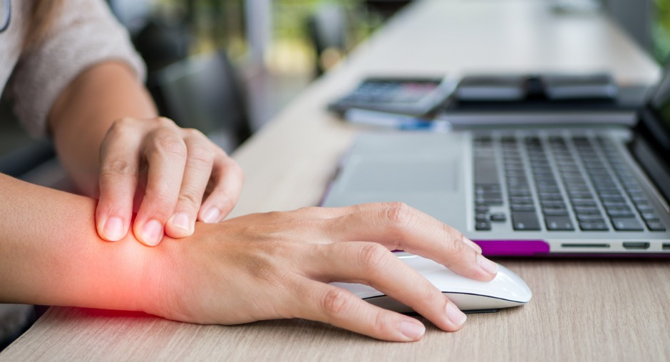 Woman holding her wrist in pain from either carpal tunnel or RSI