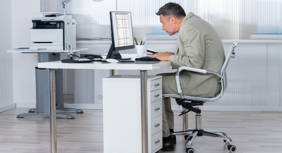 An office worker with bad posture sitting at his desk