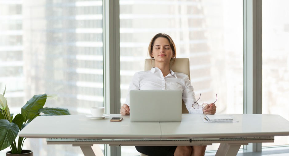 a young business woman at her ergonomic desk making sure she has the correct posture in her ergonomic chair