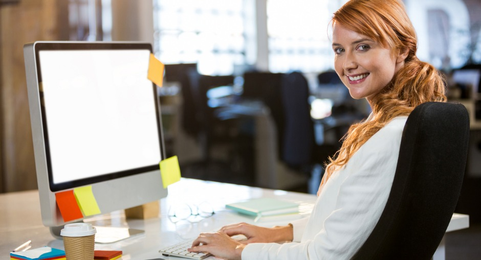 Female office worker sitting at desk typing and smiling
