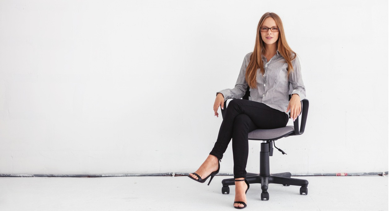 A business woman sitting in an ergonomic office chair against a white background