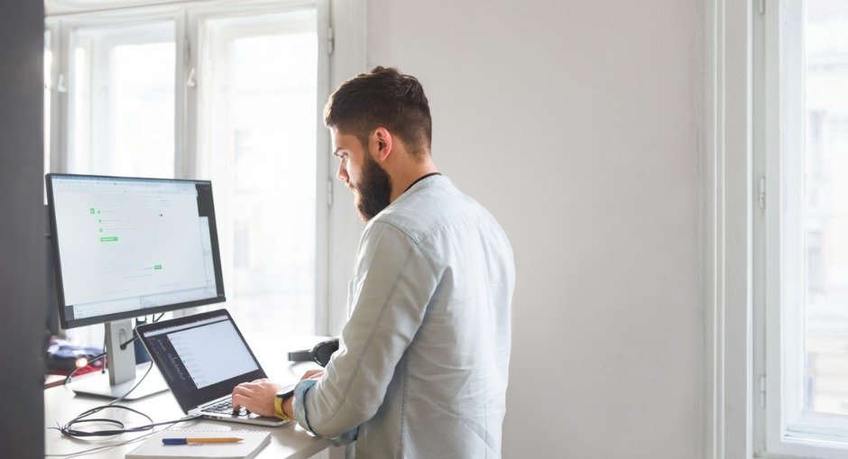 young bearded man working at his standing desk at his office